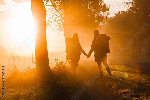 A couple of hitchhikers with backpacks at sunrise Fototapet