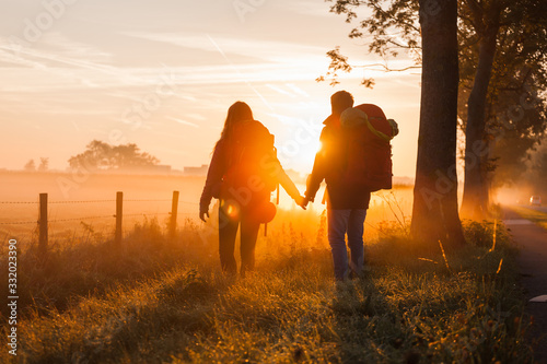 Fotografiet A couple of hikers with backpacks at sunrise