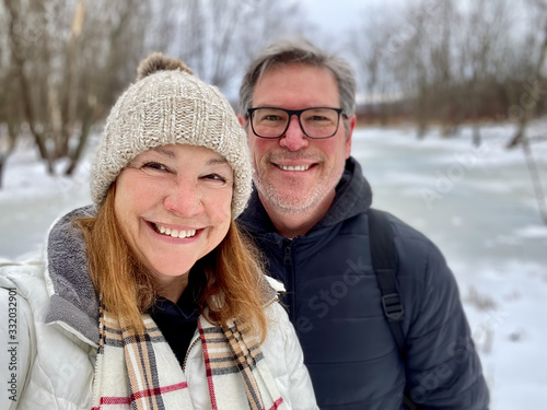 Fototapeta Happy middle aged couple taking a selfie outdoors in winter obraz