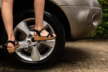 Topic Of Problems With The Car On The Road. Legs Of A Woman Forcing To Loosen Bolts Of The Car Tire. Roadside Assistance Concept