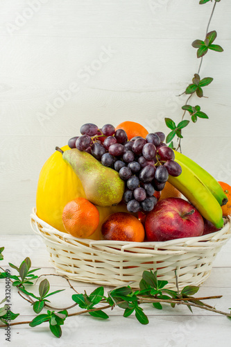 basket of fruit on white background melon  pears, oranges , grapes , apple , mandarin
