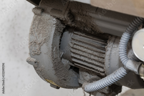 An old dusty and dirty industrial three phase electric steel motor and large heat sink, mounted under a machine Canvas Print