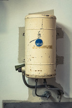 Old Electric Hot Water Service Tank With Pipes And Taps Over A Sink, Mounted On A Painted Wall In A Factory.