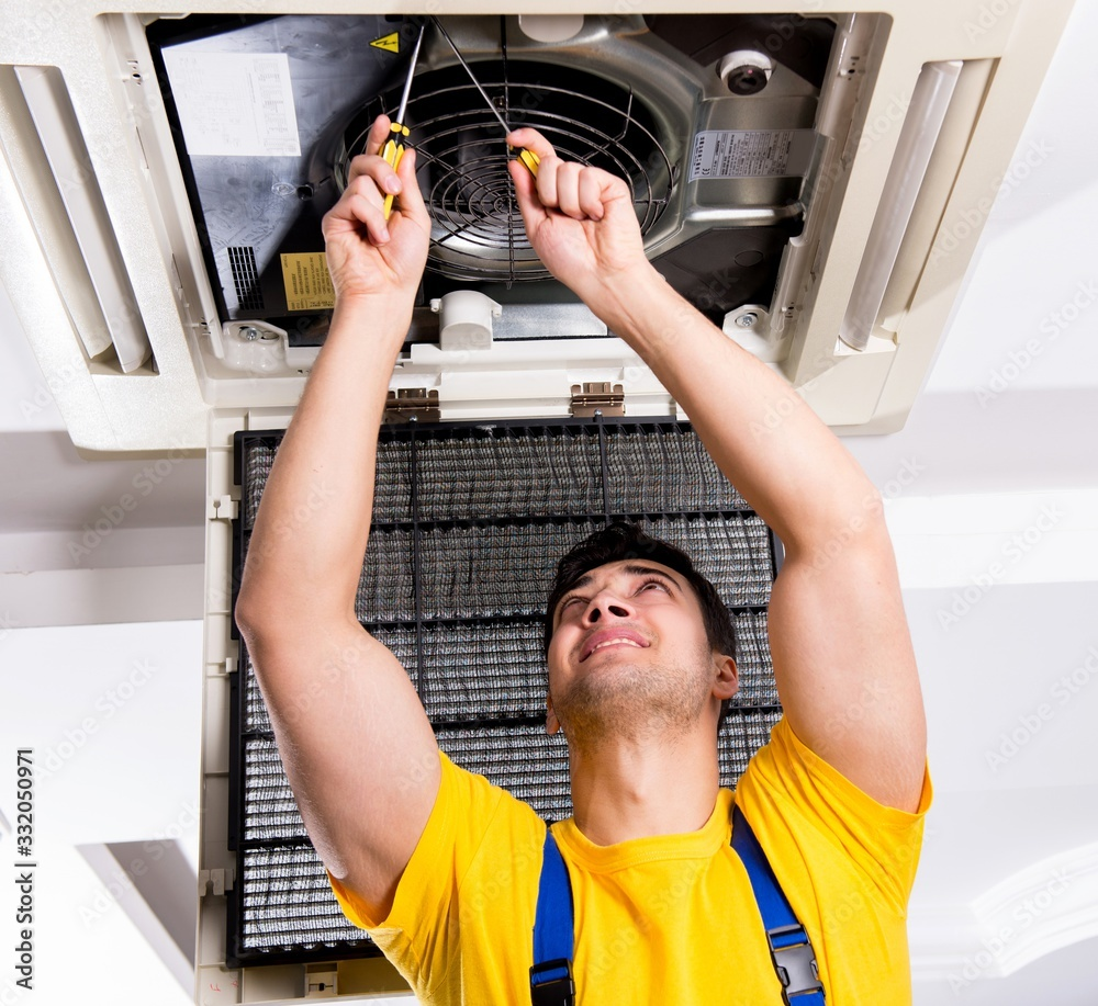 Fototapeta Repairman repairing ceiling air conditioning unit