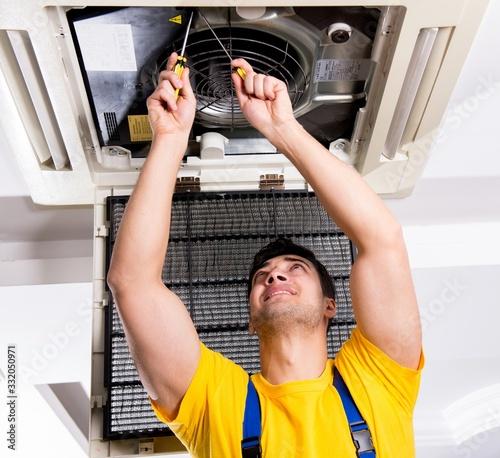 Obraz Repairman repairing ceiling air conditioning unit - fototapety do salonu