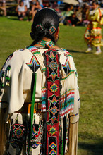 Native Indian Woman In Traditional Buckskin Regalia Judging A Dance Competition At A Pow Wow