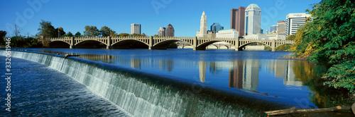 Fototapeta premium Rzeka Scioto z wodospadem i panoramą Columbus w stanie Ohio, z ustawieniem światła słonecznego