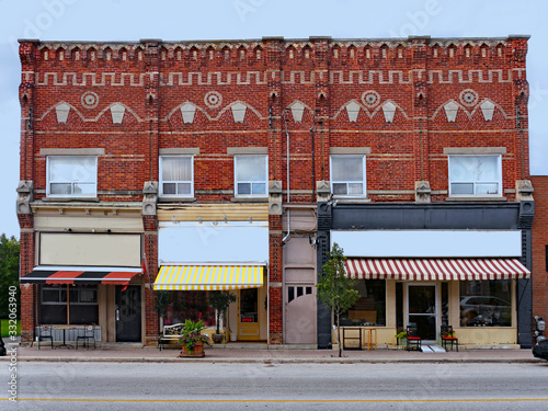 Foto Old small town Victorian building with fancy brickwork and shops with awnings