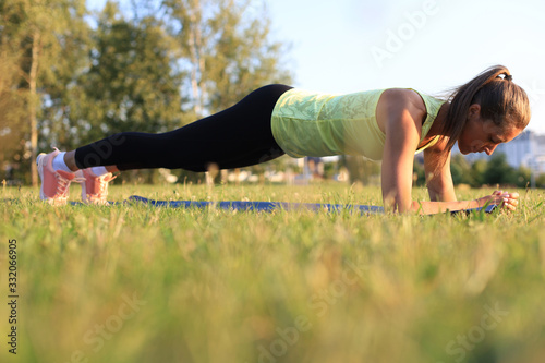 Athletic woman doing plank exercise outdoor. Work out concept. Fototapete