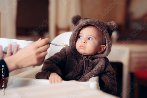 Fotografie, Tablou Funny Baby Sitting in Highchair Refusing to Eat