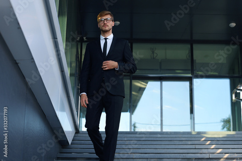 Successful young businessman walking down the stairs outside the office building Wallpaper Mural