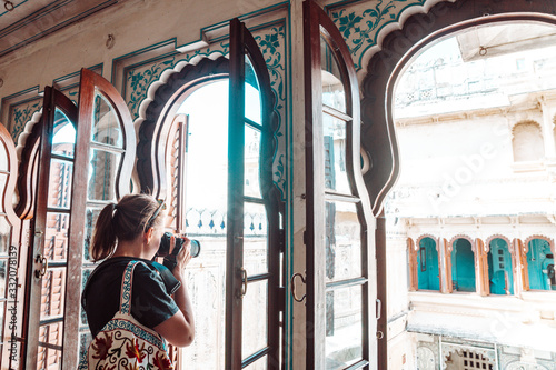 Photo Woman tourist takes photos while visiting the City Palace in Udaipur India