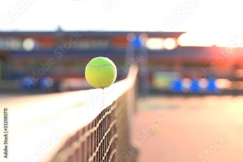 Obraz Bright greenish yellow tennis ball hitting the net. - fototapety do salonu