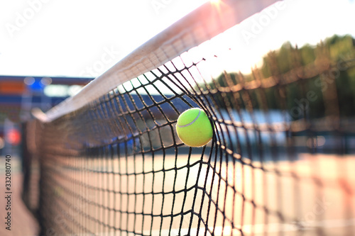 Bright greenish yellow tennis ball hitting the net. Fototapeta