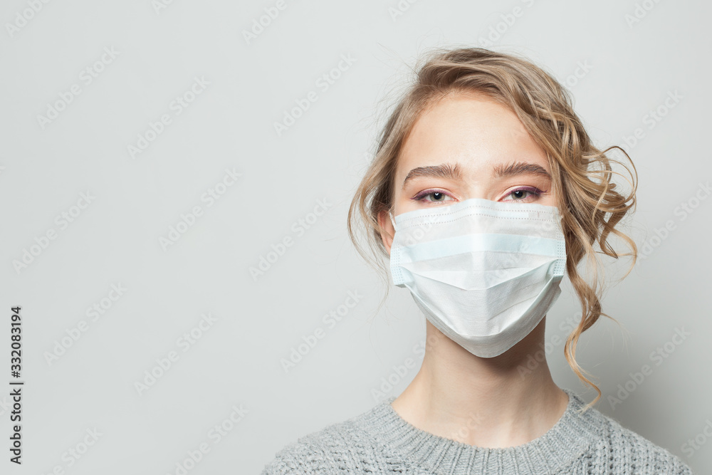 Fototapeta Young woman wearing a face mask on gray background. Flu epidemic and virus protection concept