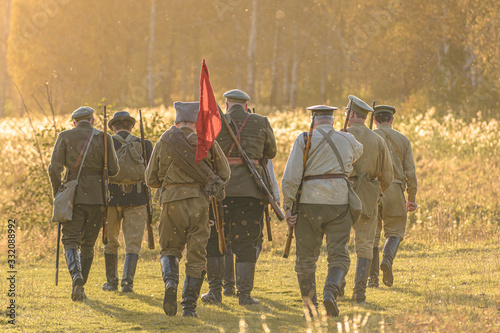 Obraz na płótnie A group of red army soldiers with a red flag goes towards the forest