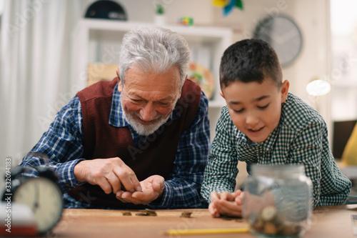 Fototapeta Grandpa and grandson saving money. Grandfather teaching grandchild how to save money. obraz
