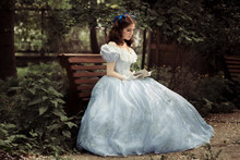 A Young Beautiful Girl In A Full Blue Dress, With Curly Hair, Is Sitting On A Bench, Holding A Book In Her Hands And Reading It. Against A Tree.Full-length Photo. Historical Reconstruction