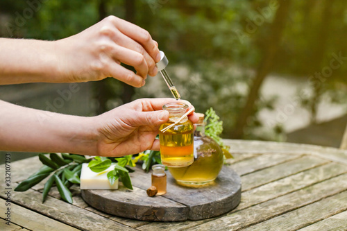 Fototapeta Concept of natural organic oil in cosmetology. Moisturizing skin care and aromatherapy.  Laboratory test outdoor, woman doing reserch and dropping extract from pipette. Wooden background, copy space  obraz