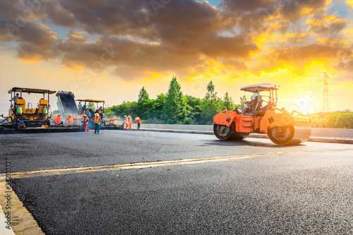 Fototapeta Construction site is laying new asphalt road pavement,road construction workers and road construction machinery scene