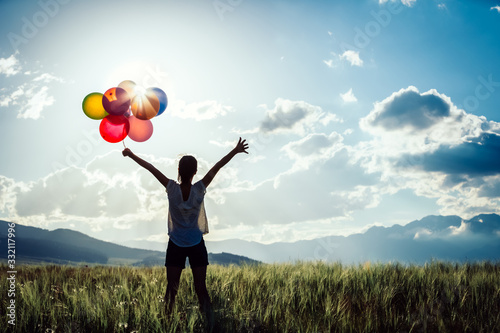 Canvastavla Cheering young asian woman on grassland with colored balloons