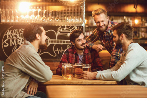 Obraz A group of friends is sitting in a bar with glasses of beer. - fototapety do salonu