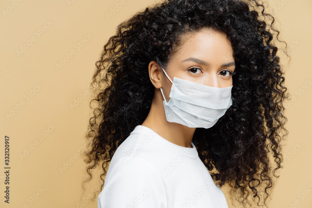 Fototapeta Photo of dark skinned Afro American woman with curly bushy hair, wears protective mask during coronavirus outbreak, isolated on beige background. Prevent disease. Virus, influenza, health care