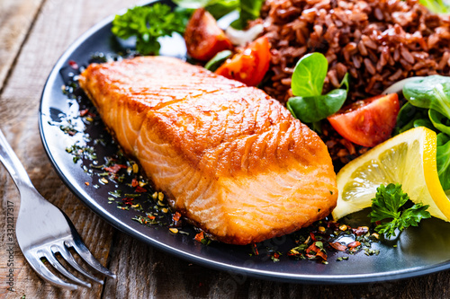 Fried salmon steak with red rice and vegetables on wooden table Fototapete