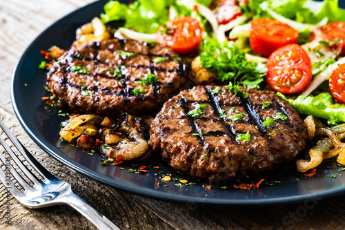 Fototapeta Barbecue steaks with vegetables on wooden background obraz