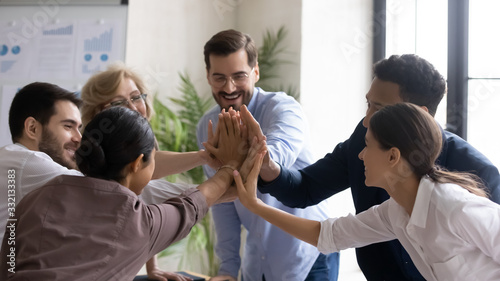Obraz Overjoyed multiracial businesspeople give high five celebrate shared business victory or win, excited multiethnic colleagues engaged in teambuilding activity at meeting or briefing in office - fototapety do salonu