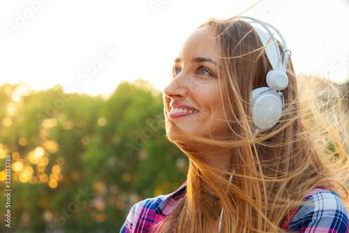 Photo Beautiful young blonde woman with long hair and blue eyes listening to music with white headpones outside