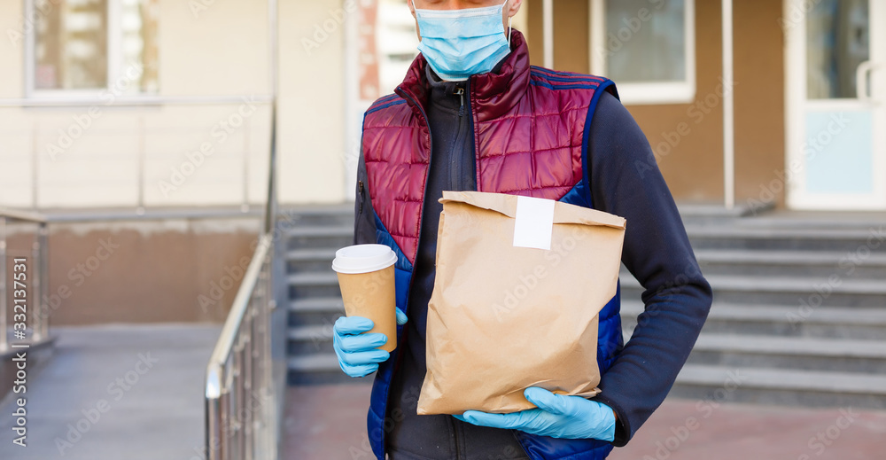 Fototapeta delivery man delivers orders. Delivery service under quarantine, disease outbreak, coronavirus covid-19 pandemic conditions.
