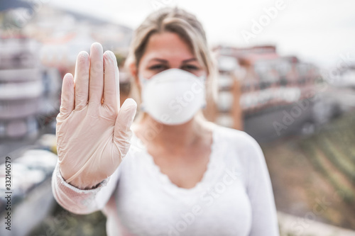 Obraz Young woman wearing face mask and latex gloves while showing stop hand gesture for coronavirus prevention -  Stop spreading Covid 19 concept - Focus on hand - fototapety do salonu