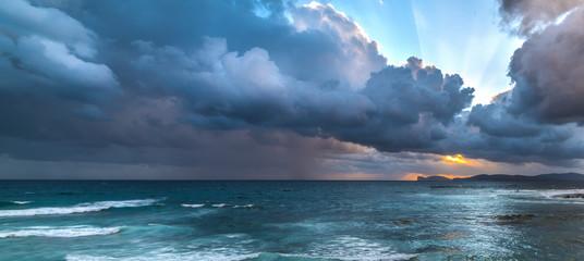 Dark clouds over Capo Caccia at sunset