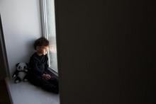 A Sad Boy Sits By The Window W...