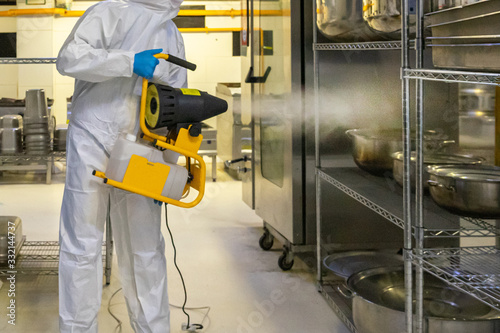 Obraz man in protective equipment disinfects with a spray gun industrial kitchen surfaces coronavirus covid-19 - fototapety do salonu