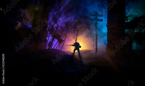 Army sniper with large caliber rifle standing in the fire and smoke Canvas Print