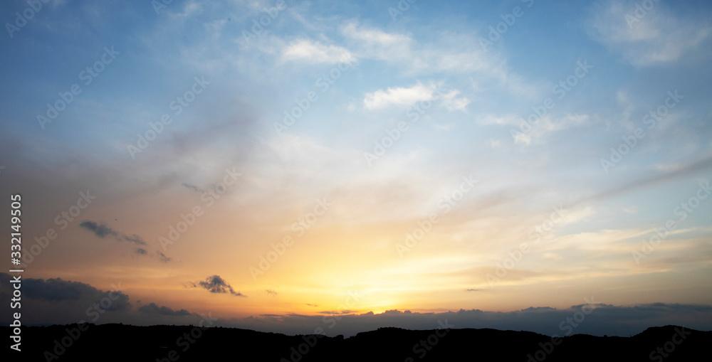 Fototapeta panoramica de una puesta de sol entre las montañas