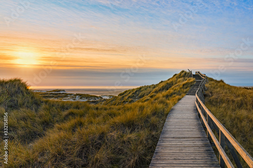 Wooden path and stairs crossing the dunes to the beach of Norddorf, Amrum, in sunset