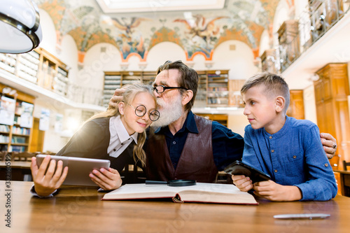 Fototapeta Elderly man teacher and his teen students, boy and girl, sitting at the table in library, reading book, using tablet and studying. Bearded man loves his students, is proud of them and kissing girl obraz na płótnie