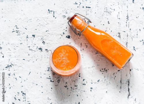 Obraz Glass and takeaway bottle with mango magic smoothies on a light background, top view.  Smoothies with ripe mango, carrot, orange, honey, ginger. Detox drink - fototapety do salonu