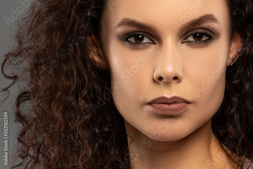Fototapety, obrazy: Young beautiful girl with curls on her head with a serious facial expression on a gray background. Portrait of a woman with a strong face with brown eyes in a pink T-shirt and red suspenders.
