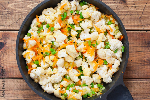 Fototapeta Step by step preparation of vegetable stew with cauliflower, step 3 - adding cauliflower, beans to the pan, top view, selective focus obraz