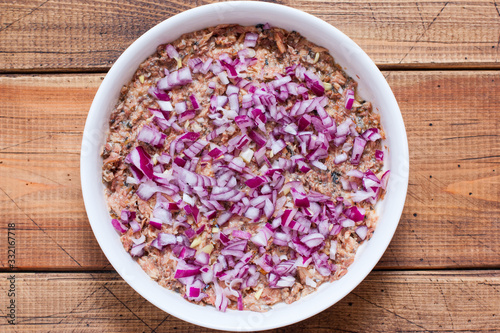Fototapeta Step-by-step preparation of a traditional Russian spring Mimosa salad, step 2 - adding chopped salad onions to the salad, top view, selective focus obraz