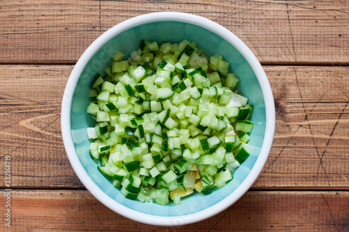 Fototapeta Step by step preparation of cold okroshka soup with sausage, step 4 - adding chopped fresh cucumber, top view, selective focus obraz
