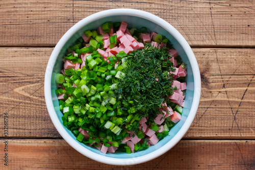 Fototapeta Step by step preparation of cold okroshka soup with sausage, step 5 - adding chopped dill and green onion, top view, selective focus obraz
