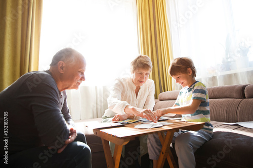 Obraz Grandparents playing board game with grandson - fototapety do salonu