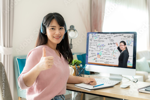 Obraz Asian woman student video e-learning with teacher on computer and thumb up in living room at home. E-learning ,online ,education and internet social distancing protect from COVID-19 viruses. - fototapety do salonu