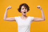 Strong young brunette woman girl in white t-shirt posing isolated on yellow orange background studio portrait. People sincere emotions lifestyle concept. Mock up copy space. Showing biceps, muscles.