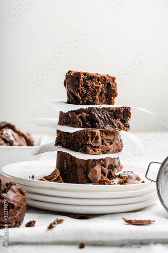 Fototapeta Healthy baked homemade brownies stacked on top of each other on four white plates and white background obraz